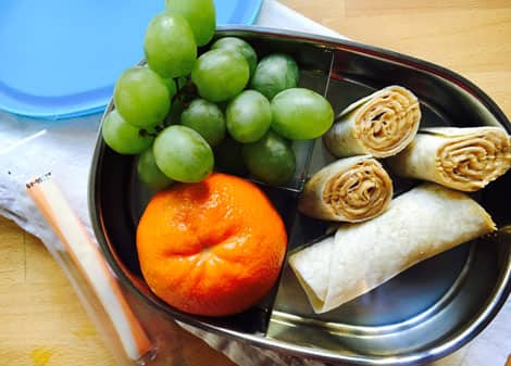 Wraps inside a small tin lunch pail, along with a bunch of grapes, a clementine and a package of string cheese.