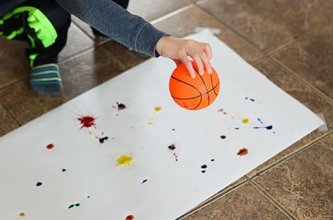Little hand dribbles a basketball as part of an art project.