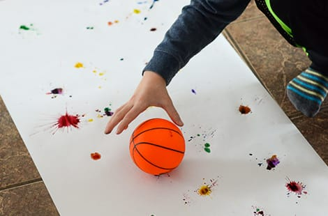Child grabs at basketball that hovers over the splatter painting.