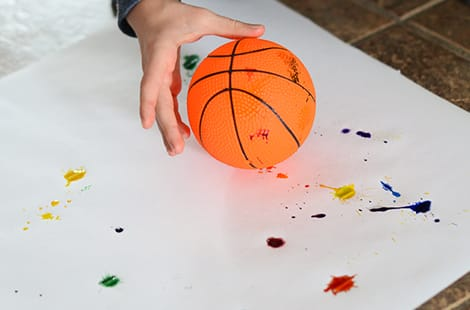Child holds basketball over top of art project.