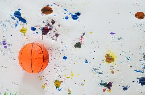 Basketball on top of painting with colourful art splatters.