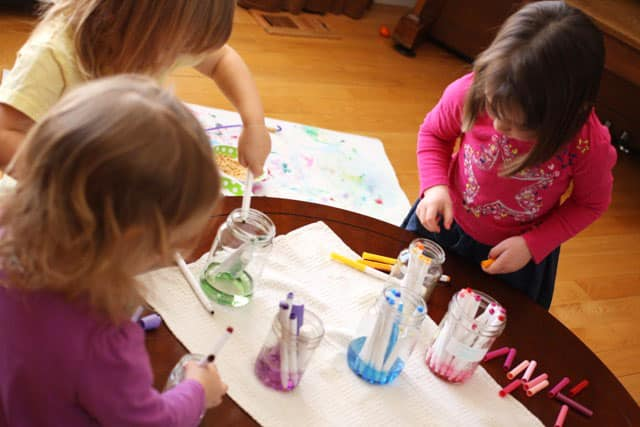 Three small kids loading markers into jars based on colour.