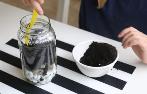 Layering dirt into the jar.