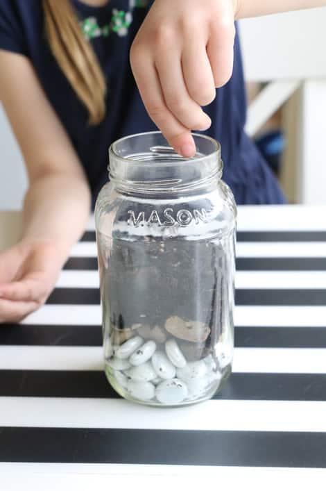 Adding seeds to the jar.