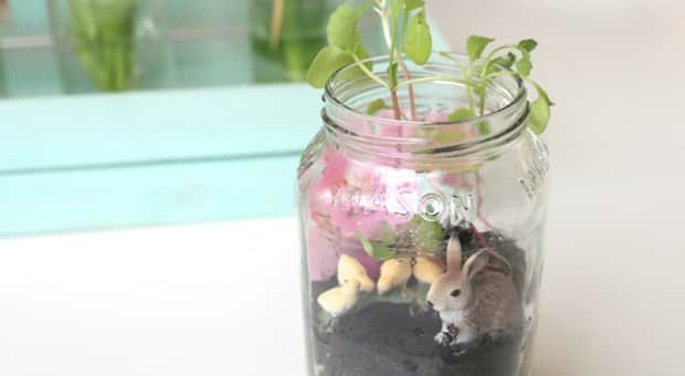 A mason jar filled with sprouted plants, a plastic rabbit figurine, a faux pink flower, soil and rocks.