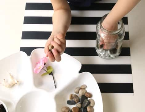 Adding rocks to the bottom of the jar.