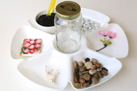 A plastic tray with needed supplies: an empty mason jar, glass rocks, dirt, radish seeds, river rocks, a fake pink flower and a plastic lamb.