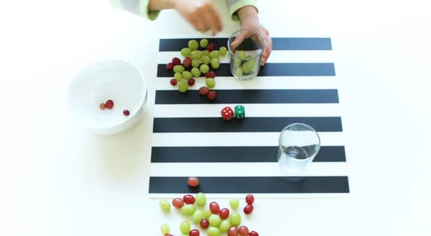 A table with grapes and 2 dice. One die reads 2, the other reads 4.