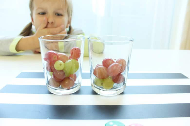 A girl looks at two cups filled with grapes. One has more grapes than the other.