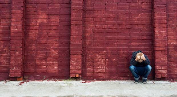 A sad boy up against a red brick wall.