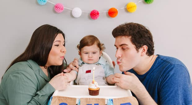 young couple with their baby on the baby's first birthday