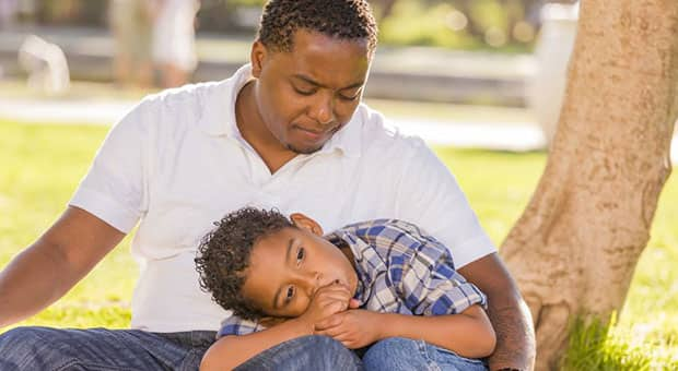 Child leans on father's lap on park bench.