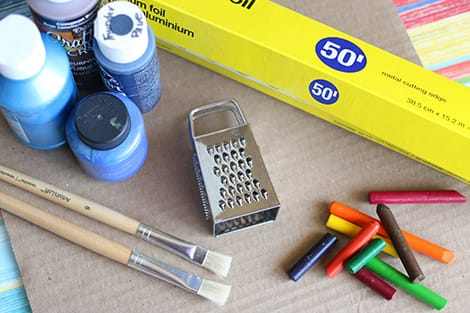 An image of all of the needed supplies: crayons, spice grater, cardboard, tin foil, blue paint, paint brushes, tape and a baking sheet.
