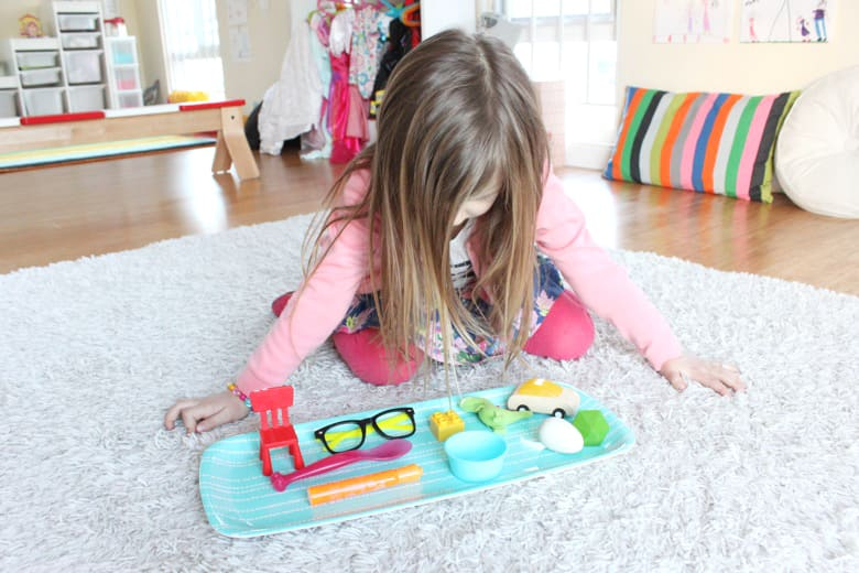 A young girl inspects a tray of objects.