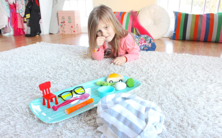 A young girl looks at a tray of objects.