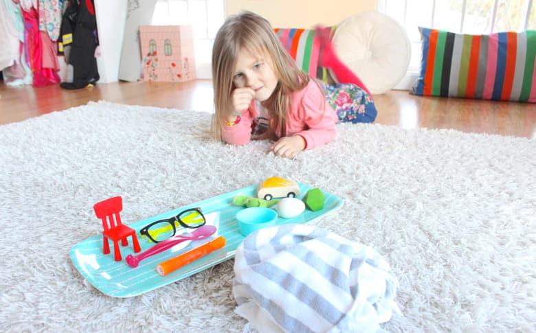 Молодая девушка смотрит на поднос объектов.