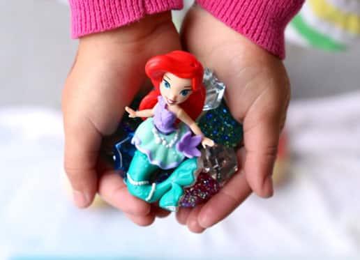 Руки ребенка, держащие русалка фигурку и выбор драгоценных камней и драгоценных камней.