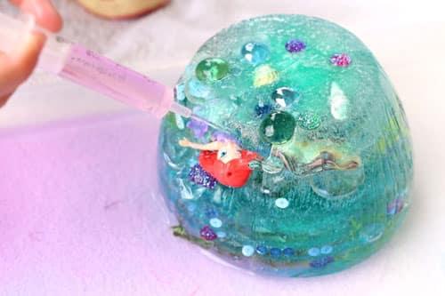 Брызги в кусок льда с помощью шприца. Голова русалки торчит из льда.