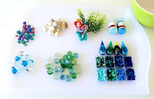 Needed supplies laid out on a plastic tray with a shallow rim: plastic and glass gems, small seashells, plastic aquarium glass, a small mermaid figurine, glitter, food colouring and sequins. A small bowl is sitting next to the tray.
