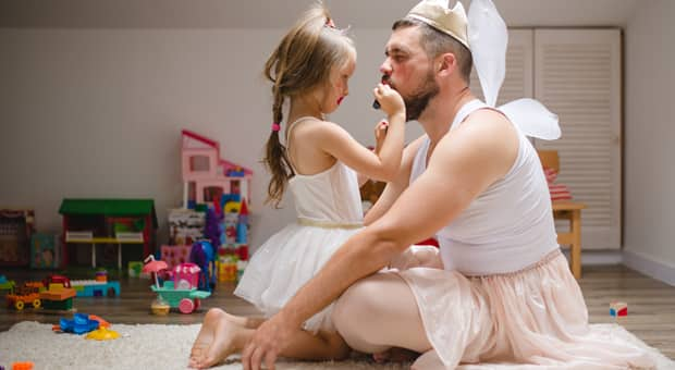 a father plays dressup with his daughter