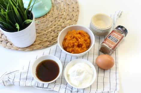 A white tabletop with a bowl of pumpkin puree, a bowl of yogurt, a bowl of maple syrup, an egg, a container of pumpkin pie spice, a stack of tart shells