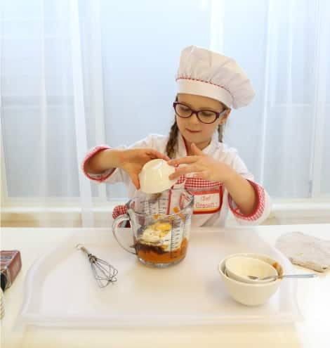 A little girl in a traditional chef hat and smock mixing all the ingredients together in a measuring cup