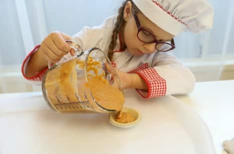 A little girl dressed in a traditional chef outfit carefully pours the mixed ingredients into one of the tart shells