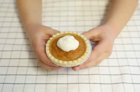 A child's hands holding one mini pumpkin pie with a dollop of whipped cream on top