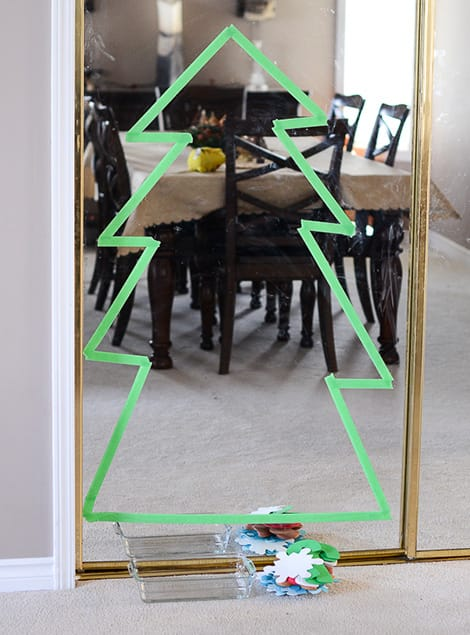 A christmas tree shape taped out on a mirror with green painter's tape.