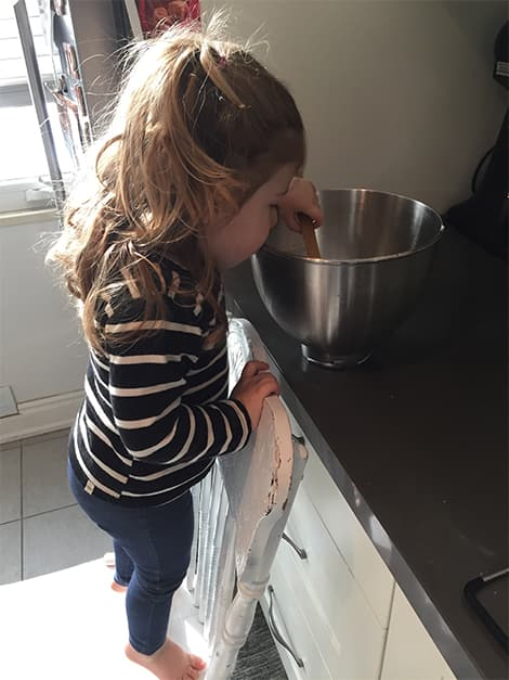 Little girl helps mix cookie dough.