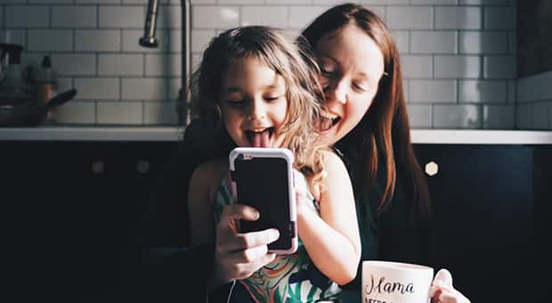 Mother and daughter pose for phone