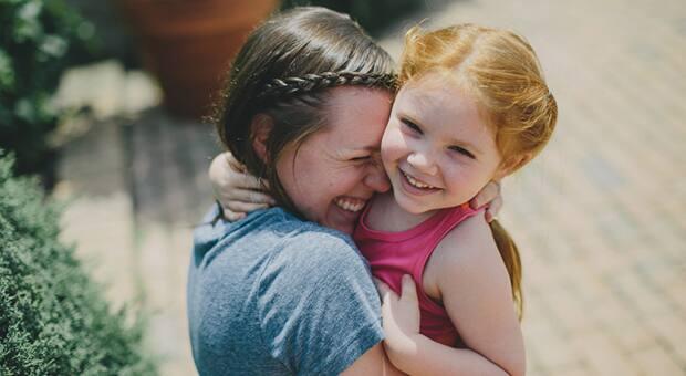 Mother hugs red-headed daughter