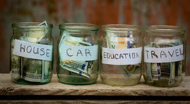 Labelled jars (travel, education, food) with money allocated into each.