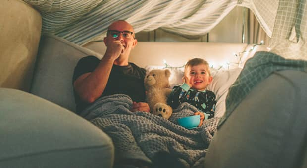 a father and son have a movie night at home in a cozy fort