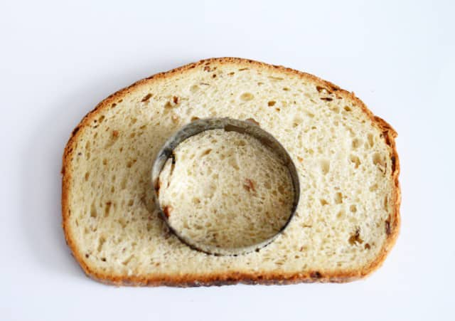 A piece of bread with a round cookie cutter on top.