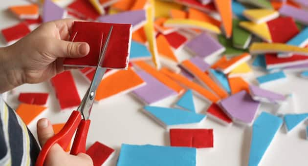 Cutting a piece of styrofoam painted red.