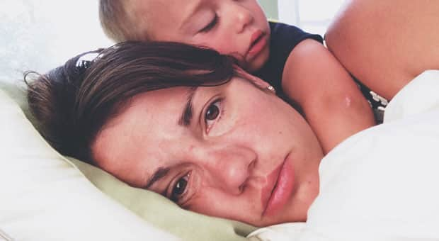 mother lies down tired and in pain while her child cuddles her
