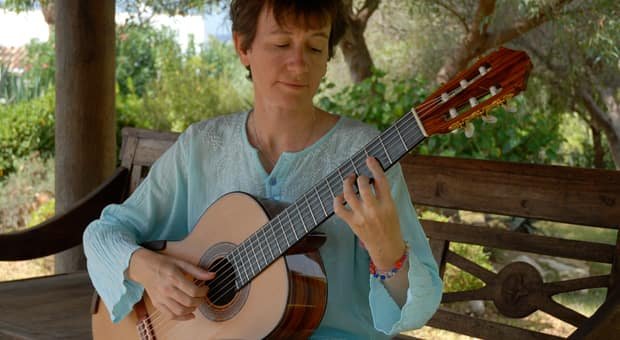 a mother practices playing guitar