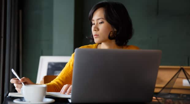 a mother sits working on a laptop