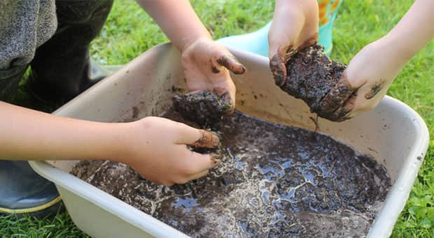 two kids playing with mud outside