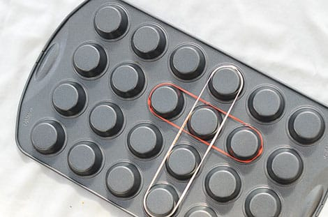 a muffin tin is turned upside down and elastics are stretched over the muffin tin nobs to create a geo board.