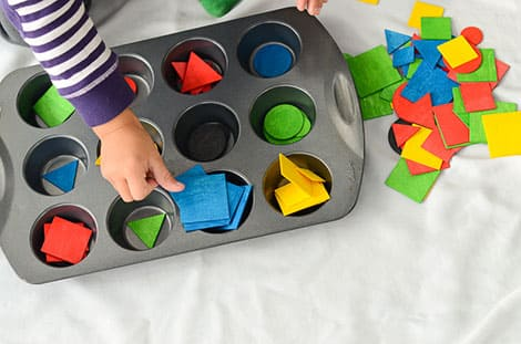 a child sorts shapes of different colours into the muffin tin