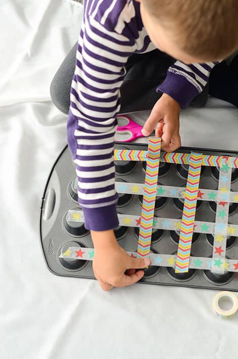 a child uses colourful tape to put on the bottom of the muffin tins