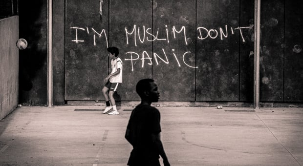 The words I'm Muslim Don't Panic are spray painted on a public wall