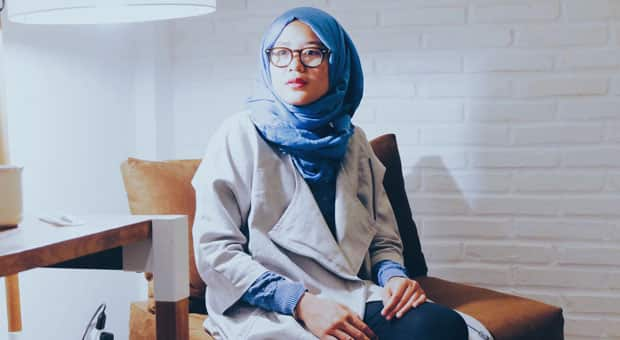 A muslim woman sits stoically