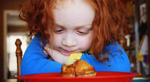 Child stares at food on plate