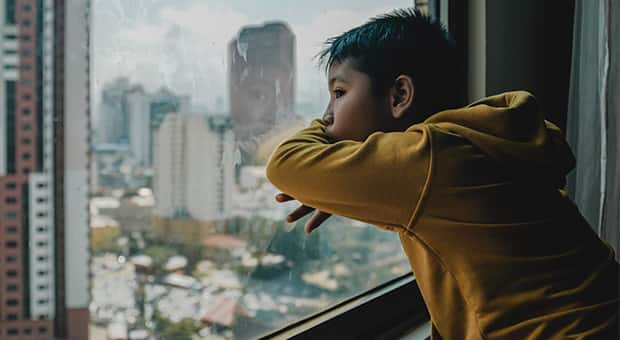 Boy looks out of condo window