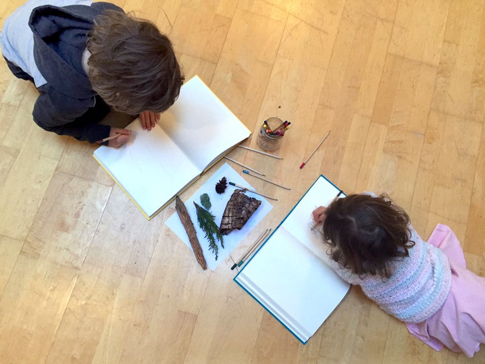 Two kids draw in their field notebooks.