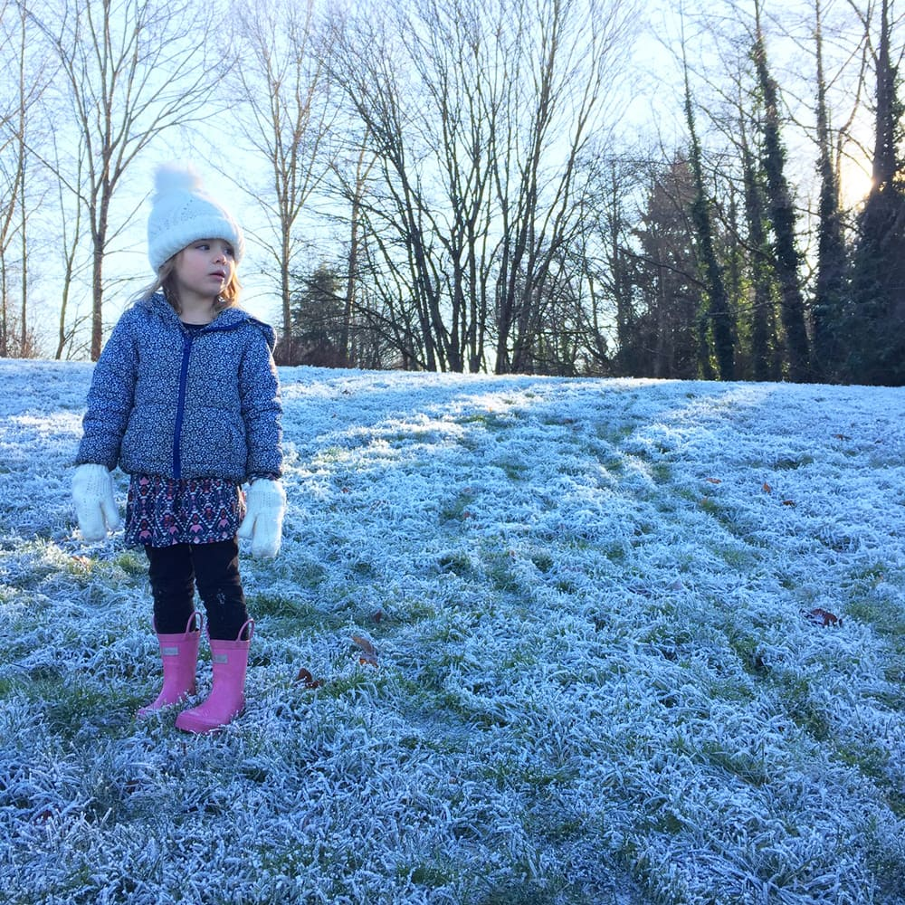 A girl stands on grass covered with snow.