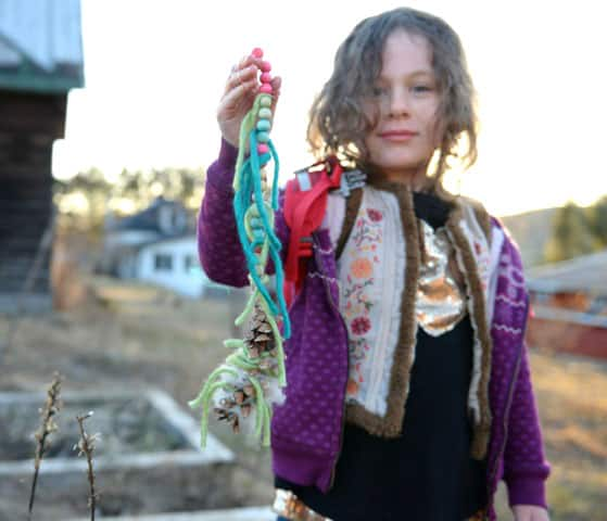 A smiling girl holding up a finished pine cone mobile.